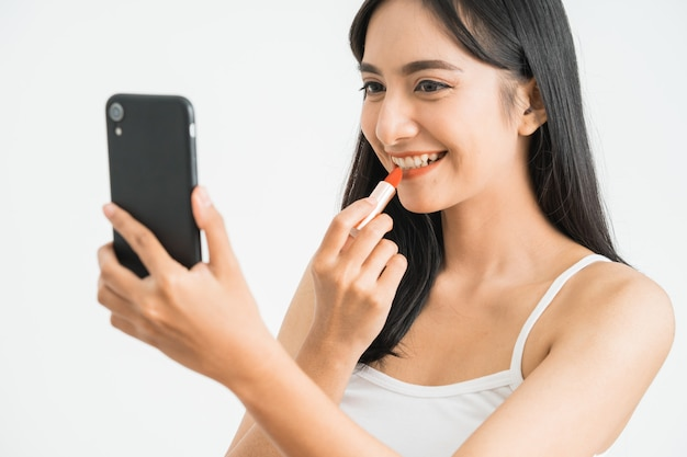 흰 벽에 거울로 그녀의 휴대 전화를 잡고 립스틱을 적용하는 아름 다운 여자. 아시아 여성 블로거