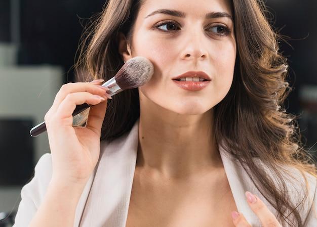 Beautiful woman applying makeup by brush