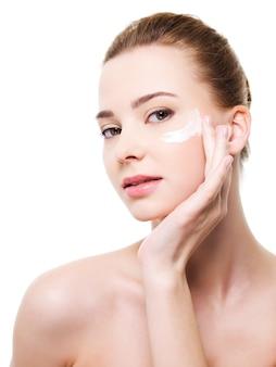 Bella donna che applica cosmetici crema idratante sotto gli occhi