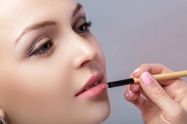 메이크업 브러시를 사용하여 핑크 립스틱을 바르는 아름다운 여성
