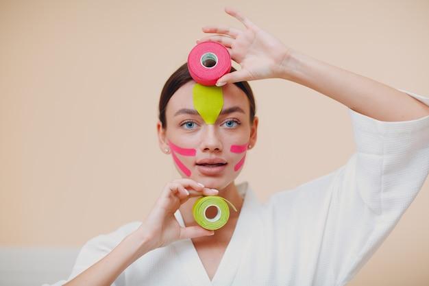 顔にテープリフティング治療を適用する美しい女性
