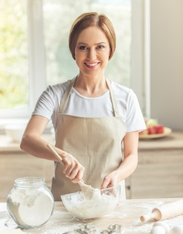 Beautiful woman in apron is looking at camera and smiling