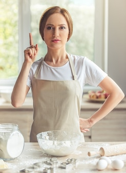 Beautiful woman in apron is looking at camera.