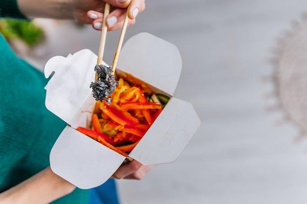 美しい女性はテイクアウトボックスからアジアのファーストフードを食べています。美味しい中華麺。