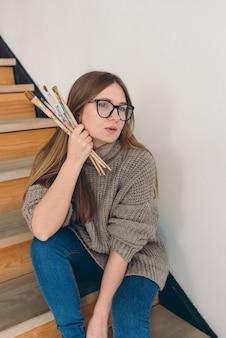 안경을 쓴 아름다운 여성 예술가와 브러시로 계단에 앉아 있는 평상복