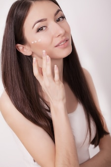 A beautiful woman asia using a skin care product, moisturizer or lotion and skincare taking care of her dry complexion.