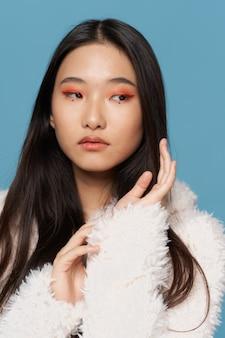 Красивая женщина азиатская внешность косметика роскошный синий фон