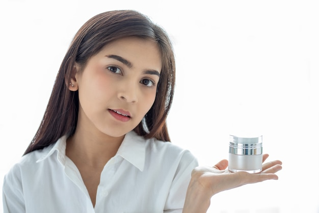 A beautiful woman asian using a skin care product, moisturizer or lotion taking care of her dry complexion.