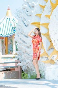 Азиатская красивая женщина в красном платье в китайский новый год