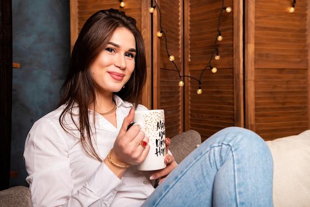 ソファに座って、コーヒーブレイク、リラクゼーションのコンセプトを持つ自宅で美しい女性。