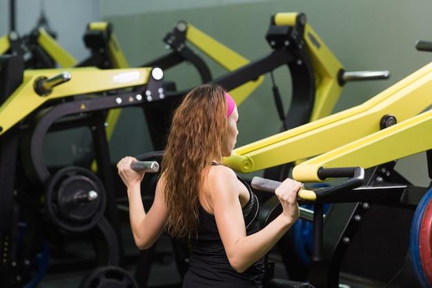 マシンで運動しているジムで美しい女性。