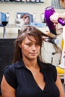 그녀의 머리카락을 건조 미용사 타격에서 아름 다운 여자