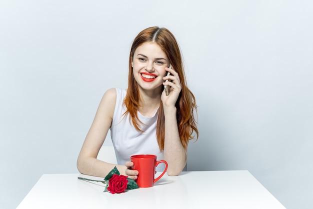 Красивая женщина за столом, светлый фон, позирует эмоции