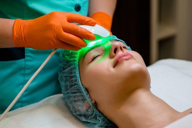 Красивая женщина на ультразвуковой уход за лицом на ультразвуковом косметологическом аппарате, аппаратной косметологии. санаторно-курортная клиника. микродермабразия. молодая здоровая кожа. омоложение кожи.