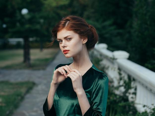 美しい女性の魅力的な外観の化粧品の緑のドレスの豪華な自然。