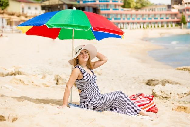 暑い晴れた日にビーチでリラックスした赤ちゃんを待っている美しい女性