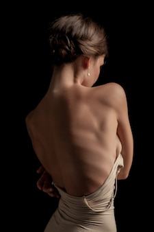 Una bella donna, vista posteriore su sfondo scuro