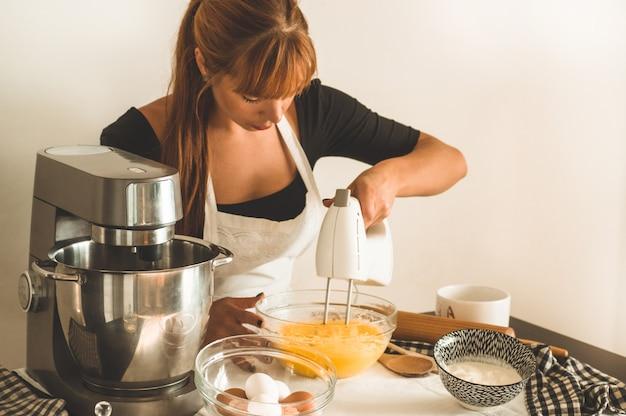 Beautiful woman bakes muffins