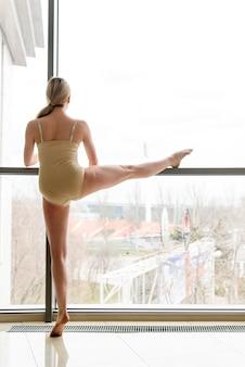 Красивая женщина-балерина танцует у окна