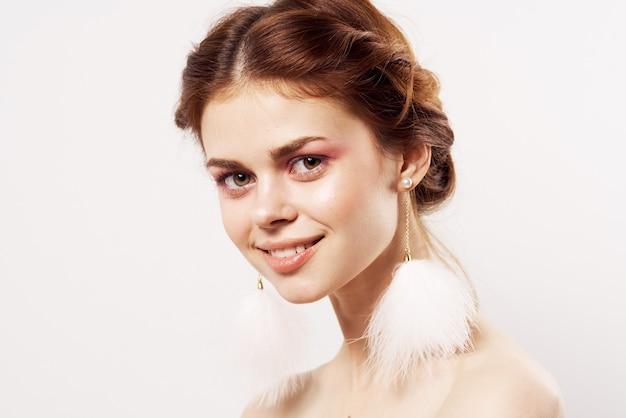 아름 다운 여자 맨 손으로 어깨 솜 털 귀걸이 매력 근접 격리 된 배경. 고품질 사진