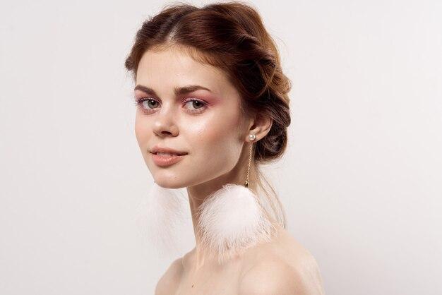 美しい女性の裸の肩ふわふわイヤリングの魅力のクローズアップ