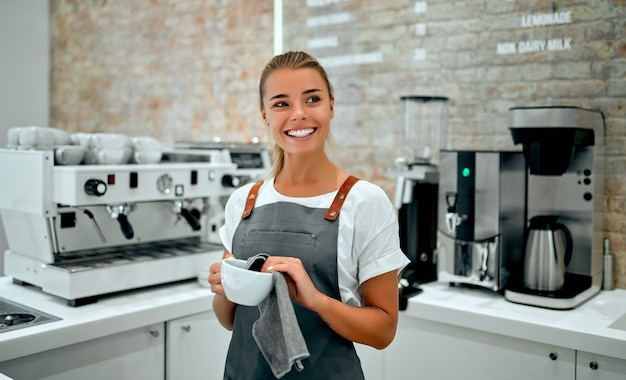 A beautiful woman barista dressed in an apron washes a cup with a rag behind the bar in a coffee shop.