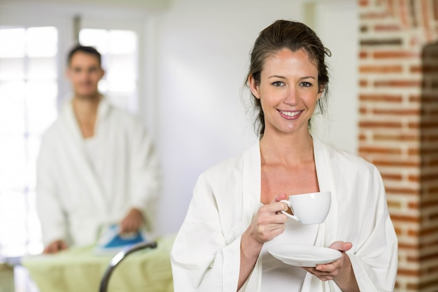 Beautiful woman in bathrobe having a cup of tea in kitchen and man ironing clothes behind her
