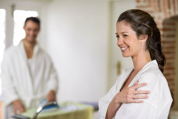 Beautiful woman in bathrobe looking away and smiling while man ironing clothes on background
