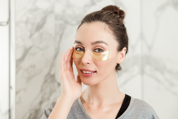 Beautiful woman in bathroom applying golden eye patches