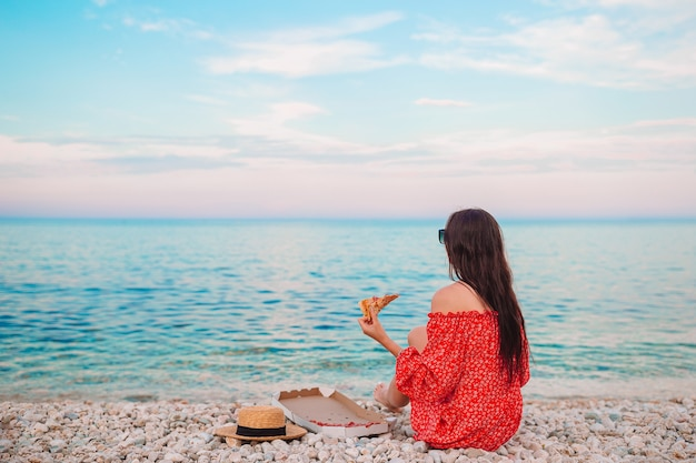 Beautiful woman on the beach on picnic with pizza