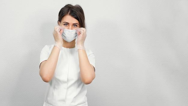Косметолог красавицы надевает белую защитную маску, стоящую у стены медицинского центра