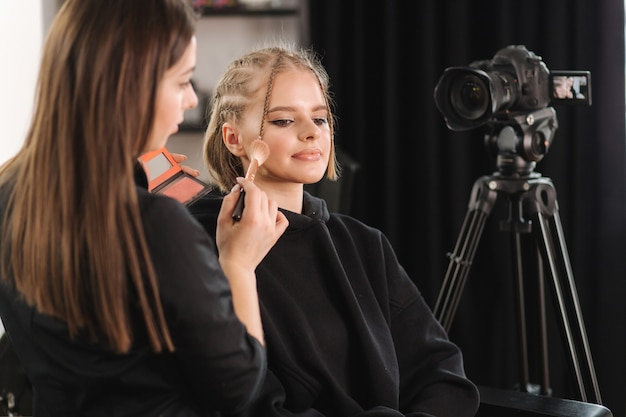 Beautiful woman beauty vlogger doing cosmetic makeup demonstration with her friend in studio
