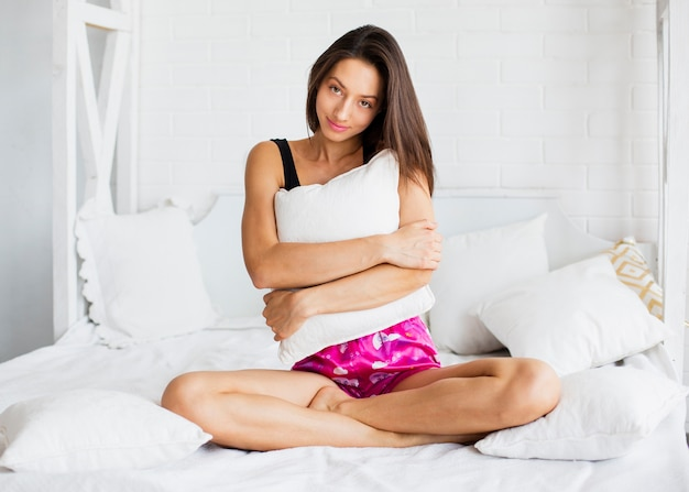 Beautiful woman in bed holding pillow