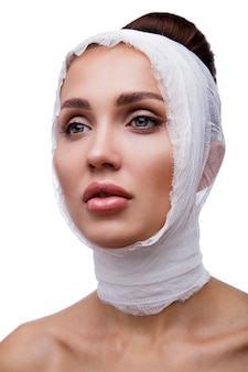 Beautiful woman before plastic surgery operation cosmetology beauty face bandages around the face