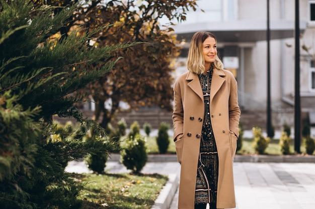 Beautiful woman in a beige coat outside in park