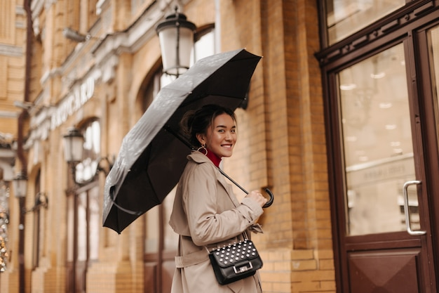 Beautiful woman in beige trench coat with cross-body bag with smile walks under umbrella in european city.