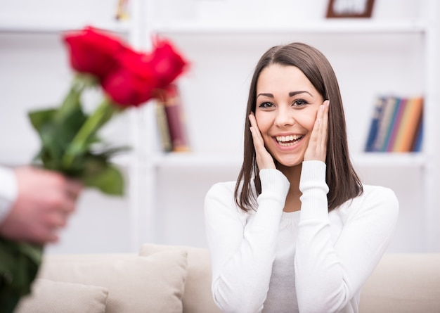 Beautiful woman being surprised with bunch of flowers.