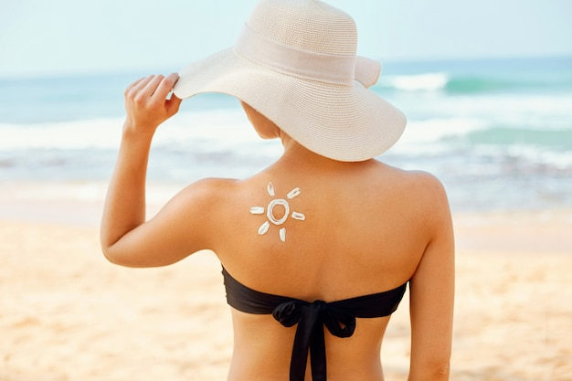 Beautiful woman in bikini applying sun cream on tanned  shoulder.