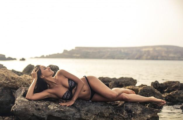 Beautiful woman in bikini on the rock