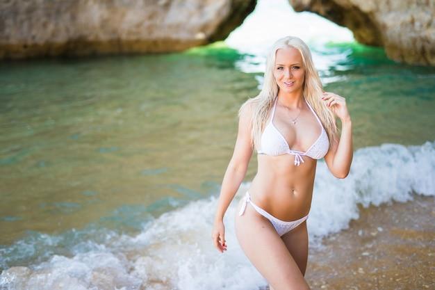 Bella donna in bikini. ragazza giovane e sportiva in posa su una spiaggia in estate