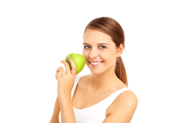 Beautiful woman biting a green apple on white background