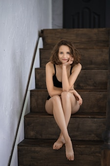 Beautiful woman in black bikini sitting on wooden stairs at home