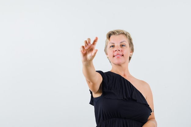 Beautiful woman in black blouse posing like showing bottle of pills
