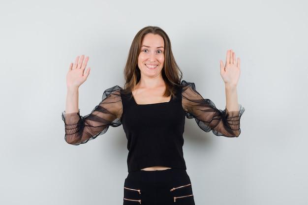 Bella donna in camicetta nera alzando le mani e guardando allegra