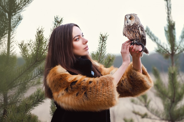 Beautiful woman in black coat with an owl