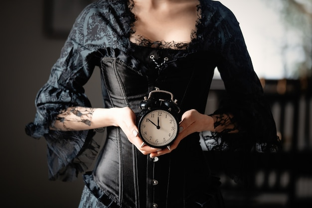 Beautiful woman in black dress holding a vintage alarm clock in indoor