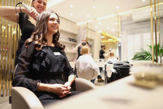 A beautiful woman in a black dress is sitting in a barber chair and smiling an experienced