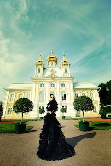 Beautiful woman in black dress posing next to the palace.