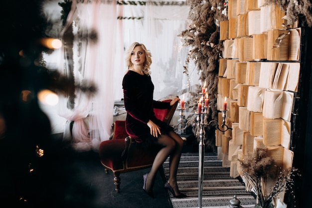 Beautiful woman in black dress sits before a wall of books and christmas decor