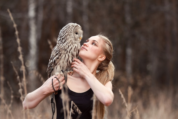 Beautiful woman in a black dress with an owl on his arm.